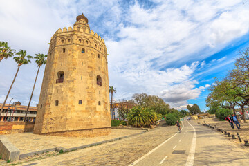 Seville, Andalusia, Spain - April 19, 2016: Golden tower or Torre del Oro with palm trees, a medieval military control tower and people cycling along the cycle path on the Guadalquivir River.