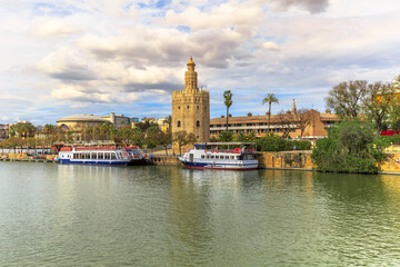 Seville, Andalusia, Spain - April 19, 2016: Golden tower or Torre del Oro, a medieval military control tower on riverside of Seville at sunset. City sightseeing from Guadalquivir River Cruise.