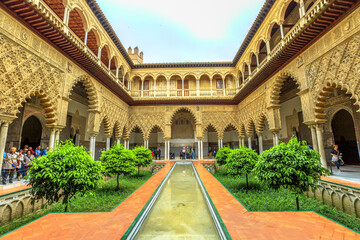 Seville, Andalusia, Spain - April 19, 2016: Patio de las Doncellas in Royal Alcazars of Seville or Reales Alcazares de Sevilla, Andalusian Architecture and old Arab Palace originally fort of Moors.