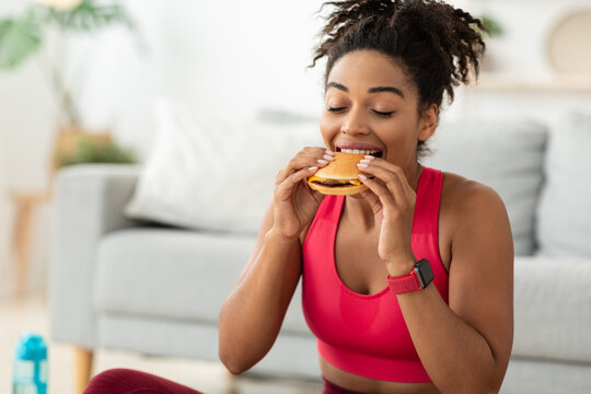 Black Fit Woman Eating Burger After Training At Home