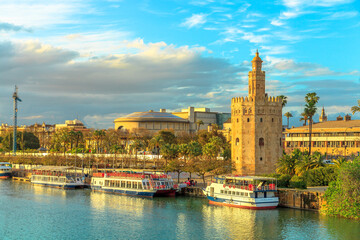 Seville, Andalusia, Spain - April 19, 2016: Golden tower or Torre del Oro, a medieval military control tower on riverside of Seville. City sightseeing from Guadalquivir River Cruise.