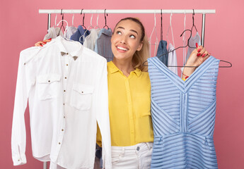 Young woman holding hangers with dress and shirt