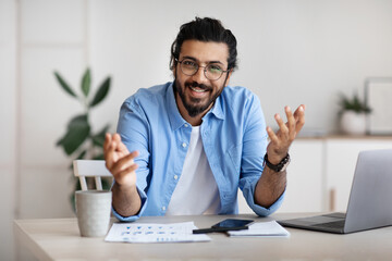 Young indian freelancer guy sitting at desk in office, talking at camera