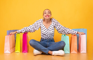 Overjoyed lady sitting with shopping bags at studio