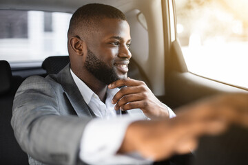Handsome black guy manager going to office by taxi