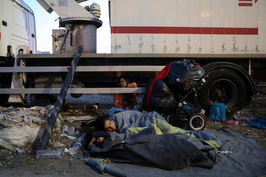 Refugees and migrants from the destroyed Moria camp sleep next to a truck, near a new temporary camp, on the island of Lesbos