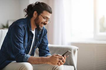 New Mobile App. Stylish Western Guy Using Smatphone At Home, Browsing Internet