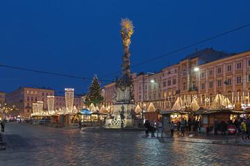 Linz, Austria. The city's main Christmas market at the Hauptplatz (Main Square) with the baroque Trinity Column in dusk.