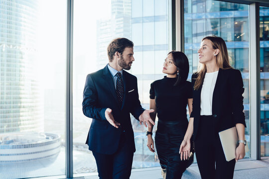 Prosperous male boss in formal wear walking in office interior with female administrative assistance discussing working process, group of woman and man colleagues talking to each other about business