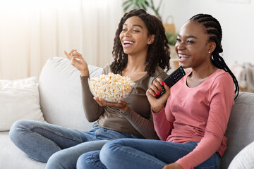 Happy african girlfriends eating popcorn and watching movie