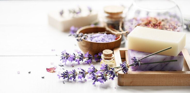 Lavender's soap and Spa products with lavender flowers on a white table.