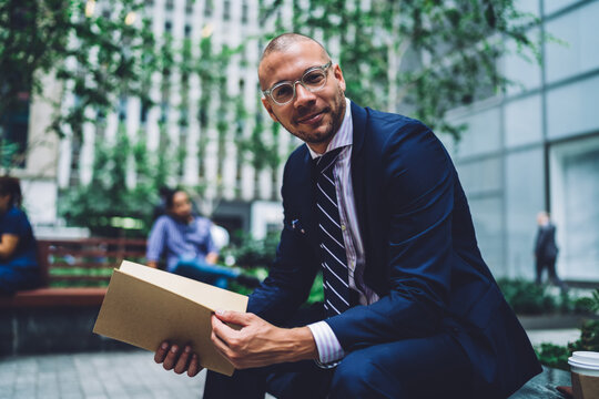 Successful male student in trendy eyewear checking details in financial course work sitting outdoors, portrait of confident man in bifocal glasses holding papers with education university project