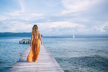 Back view of female tourist enjoying resort vacations in paradise nature environment, woman in stylish sundress walking at pier recreating during solo travelling for visiting Bora Bora island