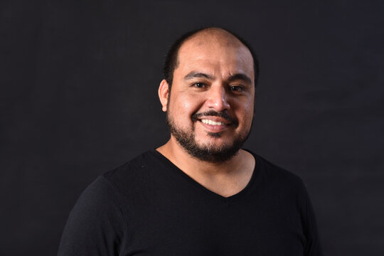 portrait of a latin american man on black  background,smiling