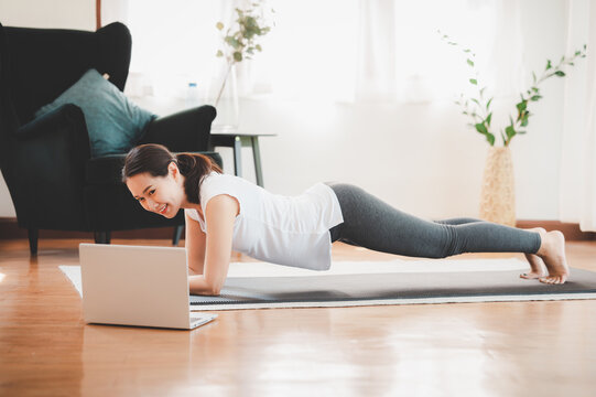 Asian woman doing plank exercise at home in a living room while watching online workout session from laptop. Fitness at home concept.