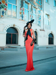 Elegant retro lady in a long red evening glamour dress. Young stylish trendy woman in a black hat with wide brim and high tulle gloves. bow at the neck. Adult woman fashion model stands on the street
