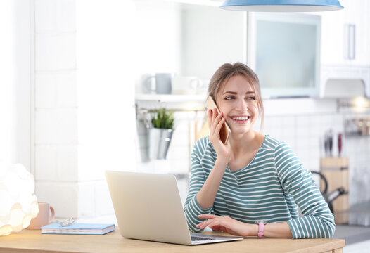 Happy young woman with laptop talking on phone at home