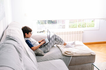 11 year old boy with laptop at home