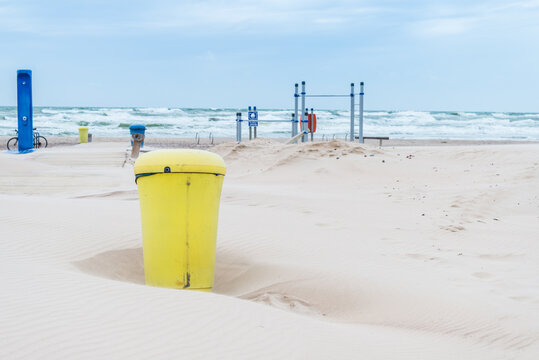 Plastic yellow dumpster can covered with sand on the beach, during the storm
