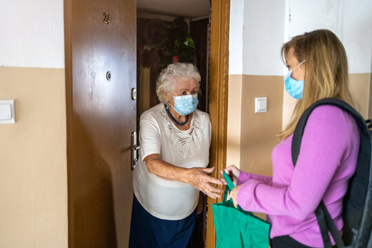 Young woman delivering groceries to her elderly grandmother