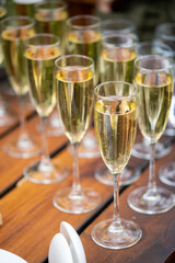 Glasses with golden champagne, bubbles and beautiful bokeh. alcoholic start to the feast. vertically.