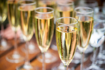 Glasses with golden champagne, bubbles and beautiful bokeh. Alcoholic set to start a party.