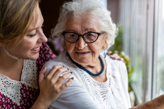 Young woman spending time with her elderly grandmother at home