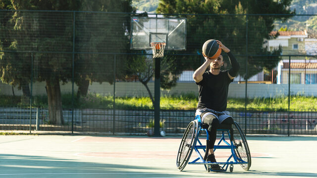 Young handsome man in wheelchair playing basketball