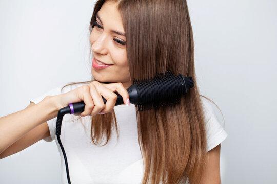 Woman With Beautiful Long Straight Hair Using Hair Straightener