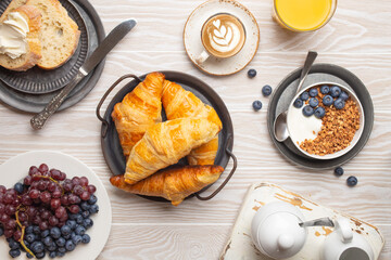 Beautiful morning breakfast with fresh croissants, granola with yoghurt and berries, toasts, coffee cappuccino and fruit on plate. Tasty and healthy breakfast on white wooden table, top view .