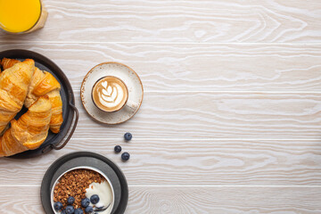 Traditional morning breakfast food on rustic white wooden background. Fresh croissants, granola with yoghurt and berries, coffee cappuccino and orange juice. Breakfast meal setting, space for text.