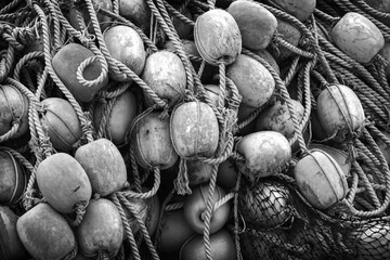 Pile of drying fishing nets with floats. Black and white