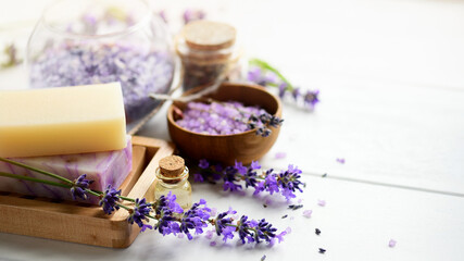 Lavender soap and Spa products with lavender flowers on a white table.