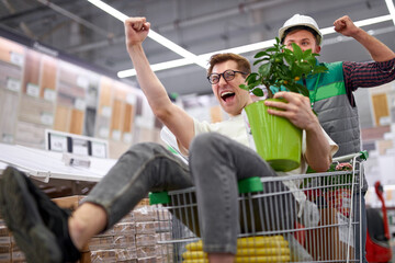 joyful customer and warehouse worker have fun in the store, young men going crazy after shopping,...