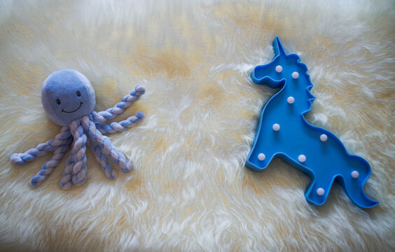 Octopus puppet and unicorn lamp on a white fur rug