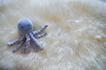 Octopus puppet on a white fur rug