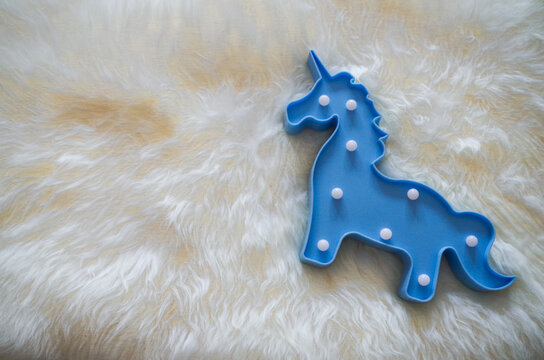 Blue unicorn lamp on a white fur rug