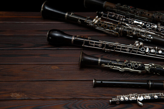 Woodwind instruments lie on a wooden surface