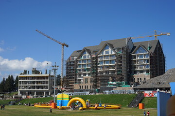 September 12th 2020, Kopaonik Serbia: Ski center in summer day view on the grand hotels in construction on the mountain range famous tourist center with people walking around