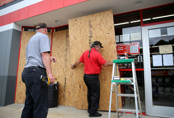 Alex Vidmar, left, and Darrin Manning board up a business as Hurricane Sally approaches in Ocean Springs