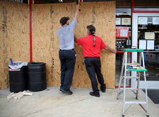 Alex Vidmar, center, and Darrin Manning board up a business as Hurricane Sally approaches in Ocean Springs