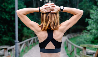 Unrecognizable athlete woman doing stretching arms outdoors