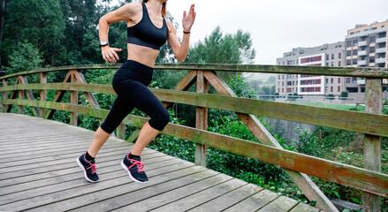 Unrecognizable athlete woman running through an urban park