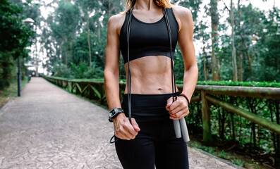 Unrecognizable athlete woman posing with skipping rope in a park