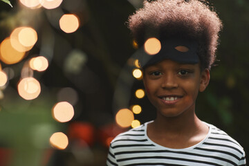 Portrait of smiling African-American boy looking at camera during outdoor Halloween party with...