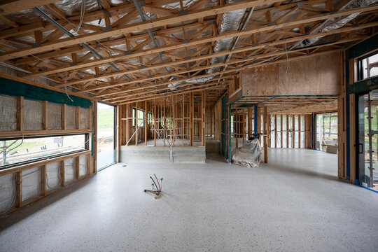 Interior view of a modern house undergoing construction, with timber frames, sliding glass doors and trusses