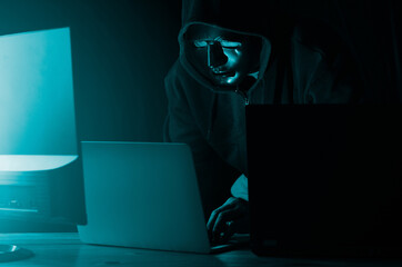 Hacker and malware concept. Dangerous Hooded hacker man using laptop Hacking the Internet.