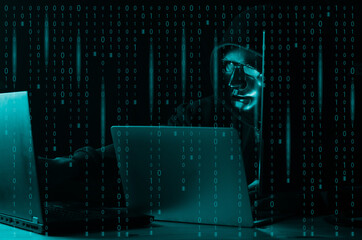 Hacker and malware concept. Dangerous Hooded hacker man using laptop with binary code digital interface.