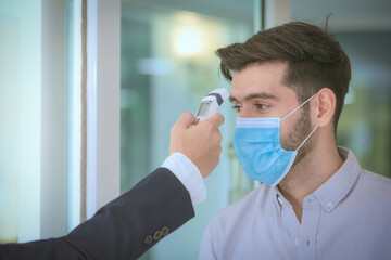 Body temperature check,Receptionist and guest wearing face mask at front desk while having...
