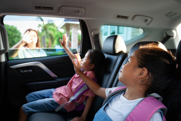 Back to school. Asian pupil girl with backpack and her sister sitting in the car and waving goodbye to her mother to get ready to school.
